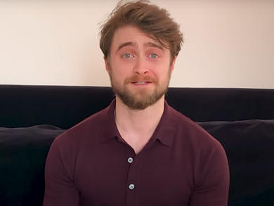 Daniel Radcliffe is reading Harry Potter and the Philosopher's Stone from his sofa